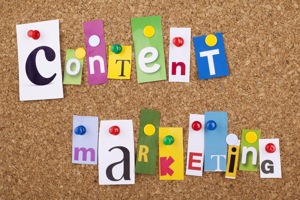 """Die einzelnen Buchstaben des Wortes """"Content Marketing"""" mit Nadeln an eine Pinnwand geheftet."""