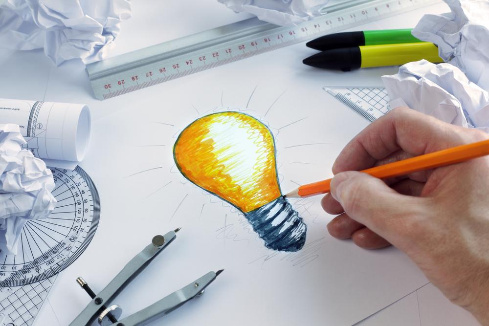 Eine von Hand gezeichnete Glühbirne und verschiedene Utensilien zum Zeichnen