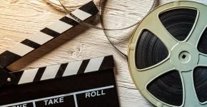 Filmrolle und Filmklappe auf Holztisch