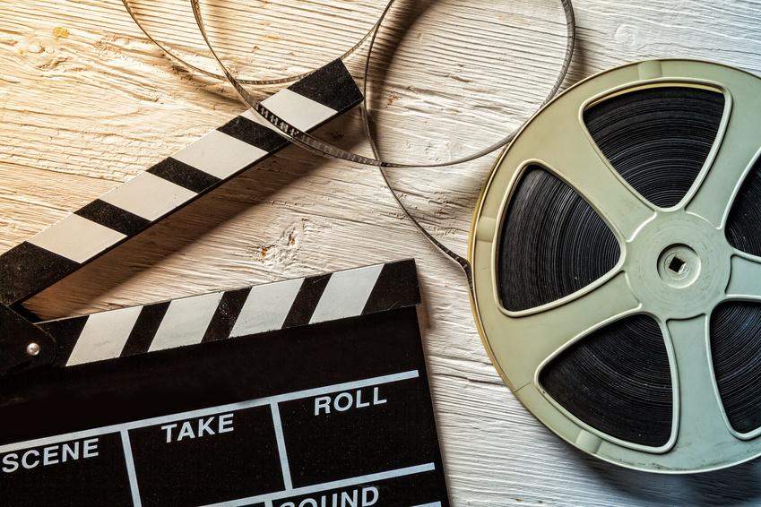 Filmrolle und Filmklappe für Unternehmensvideos auf Holztisch