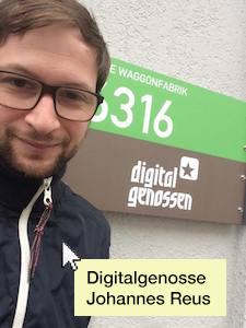 Johannes Reus vor dem Eingangsschild der Agentur Digitalgenossen